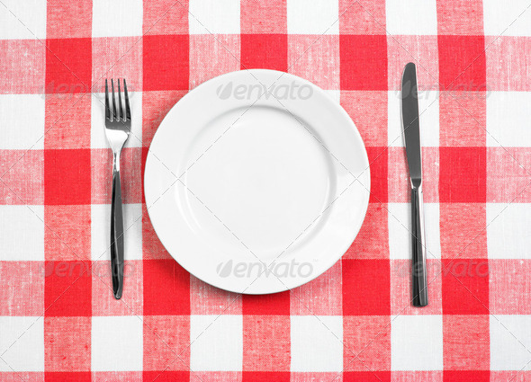 Knife, white plate and fork on red checked tablecloth - Stock Photo - Images