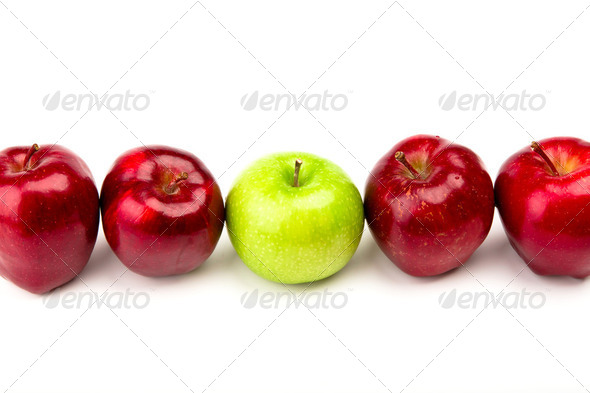 Green apple among red apples isolated on a white - Stock Photo - Images