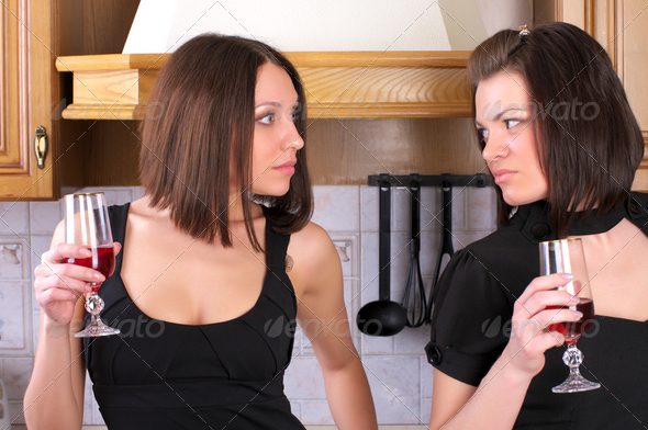 Two pretty female have an argument in the home kitchen - Stock Photo - Images
