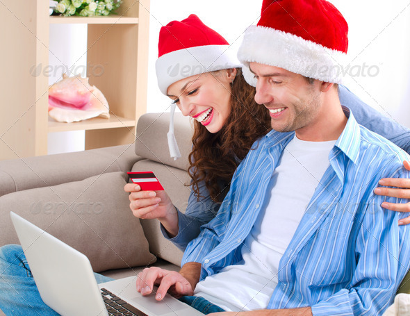Young couple with laptop and credit card buying online - Stock Photo - Images
