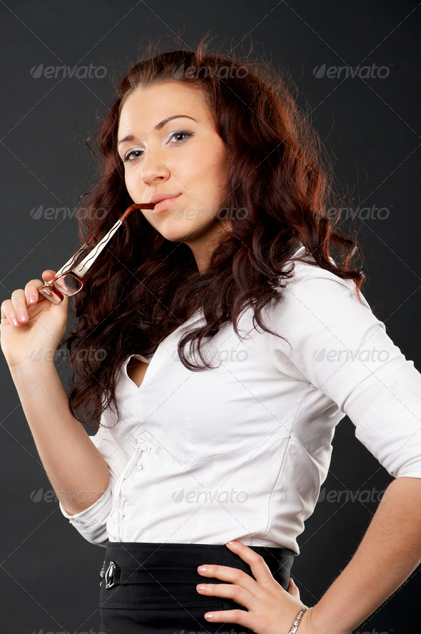 Portrait of young female holding glasses in hand - Stock Photo - Images