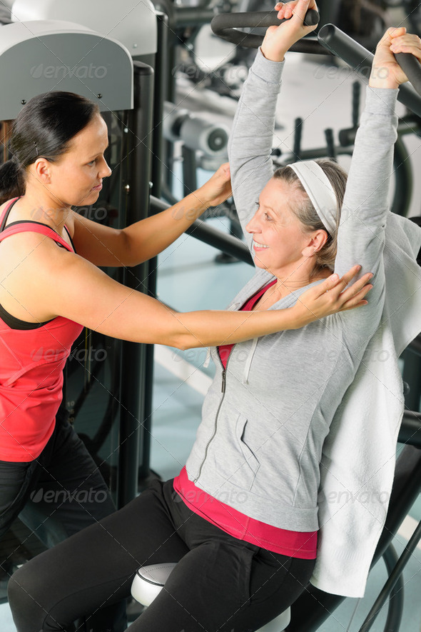 Senior woman at fitness center with trainer - Stock Photo - Images