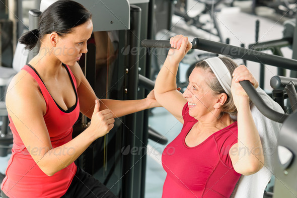 Personal trainer assist senior woman at gym - Stock Photo - Images