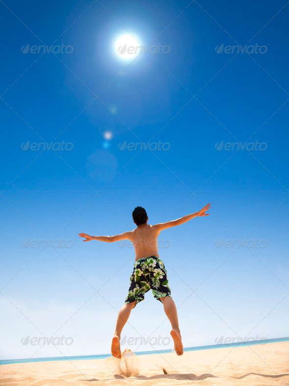 happy young man jumping on the beach - Stock Photo - Images