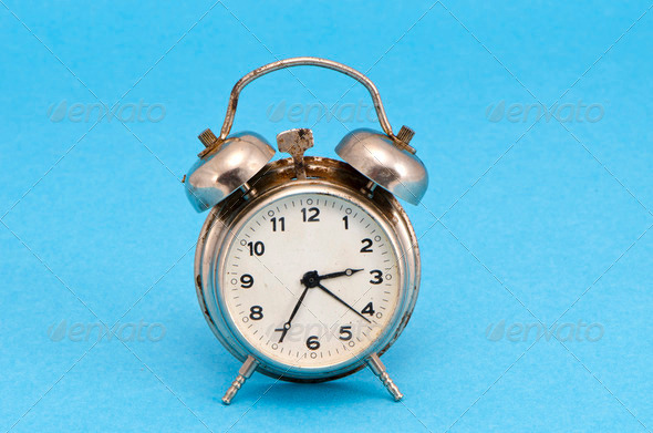 Retro grunge rusty alarm clock blue background - Stock Photo - Images