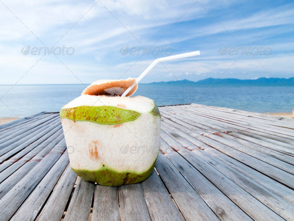 Coconut Water Drink on bamboo table with sea background - Stock Photo - Images