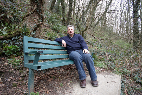 Mature man sitting on a bench - Stock Photo - Images