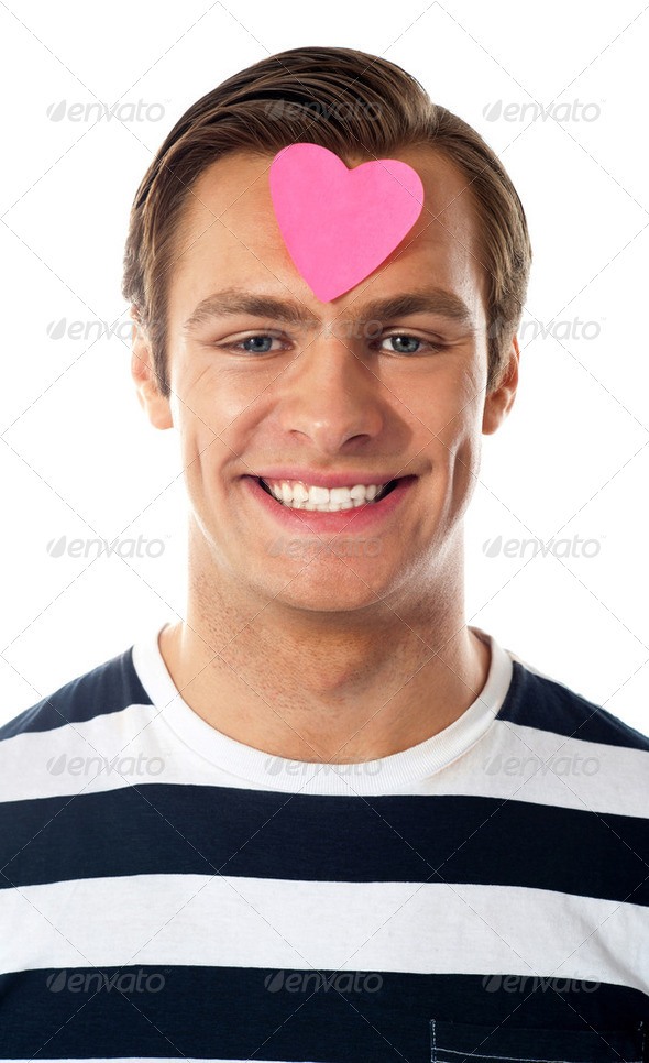 Closeup of an attractive man with paper heart - Stock Photo - Images