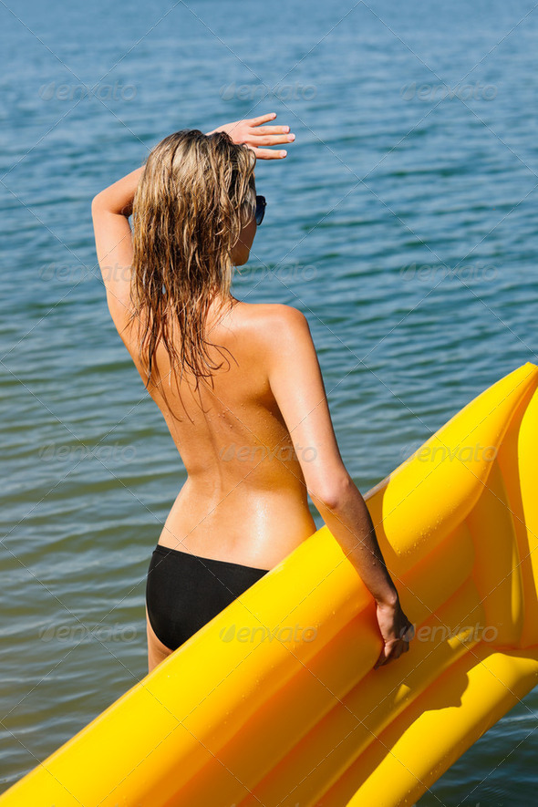 Summer woman by sea water floating mattress - Stock Photo - Images