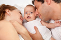 Loving parents with their cute little girl on bed - PhotoDune Item for Sale