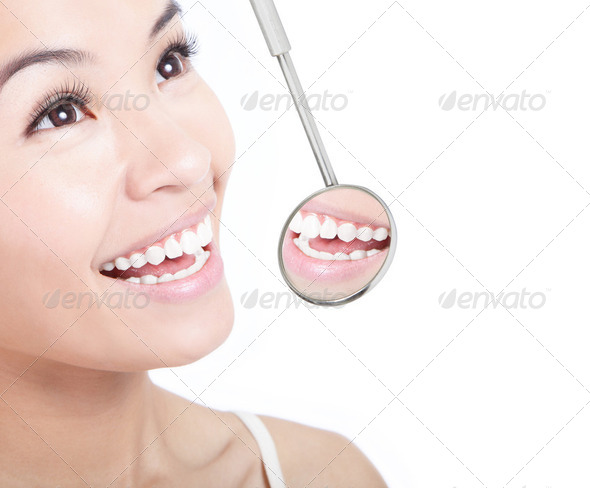 Healthy woman teeth and a dentist mouth mirror - Stock Photo - Images