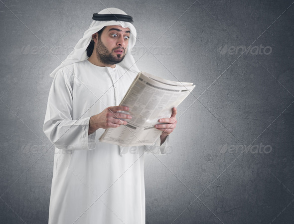 arabian businessman shocked while reading newspaper  - Stock Photo - Images