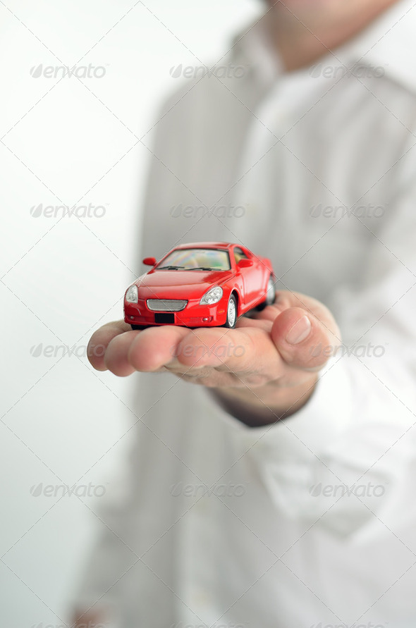 Man holding a toy car on his hand - Stock Photo - Images