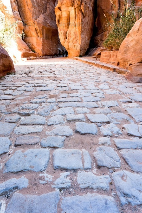 antique roman cobbled road in Siq passage in city Petra - Stock Photo - Images