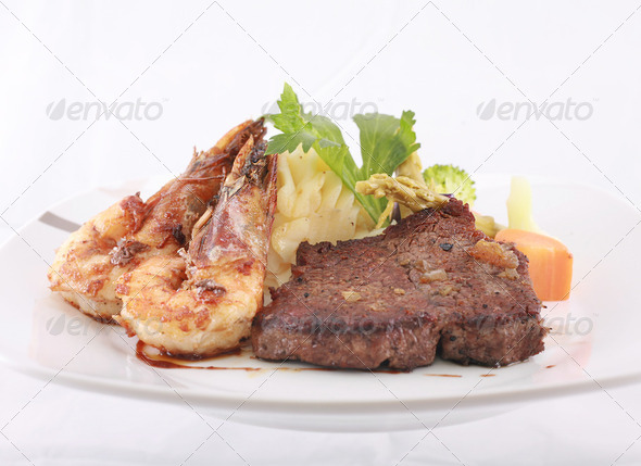 A steak and shrimp dinner over a plaid tablecloth - Stock Photo - Images