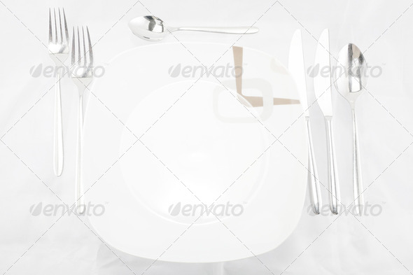 Plates with a silver fork, spoon, dessert spoon and a knife - Stock Photo - Images