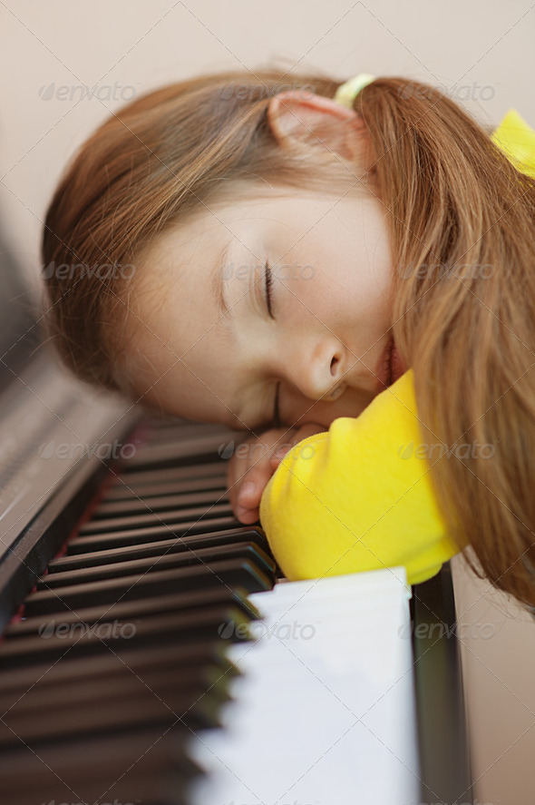 little girl in yellow dress asleep on piano - Stock Photo - Images