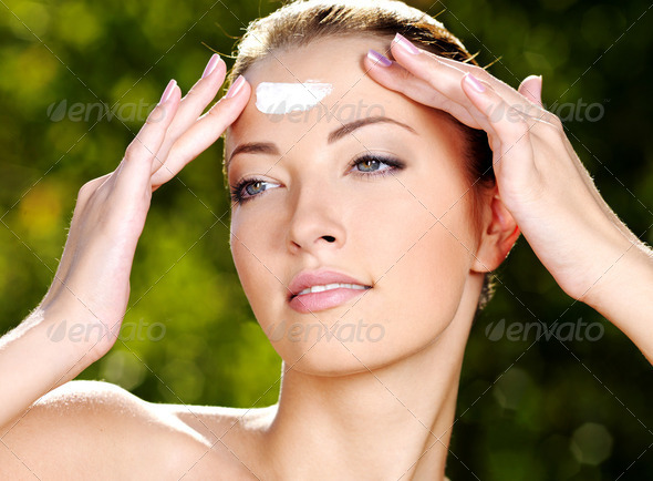 Beautiful woman applying cream on forehead - Stock Photo - Images
