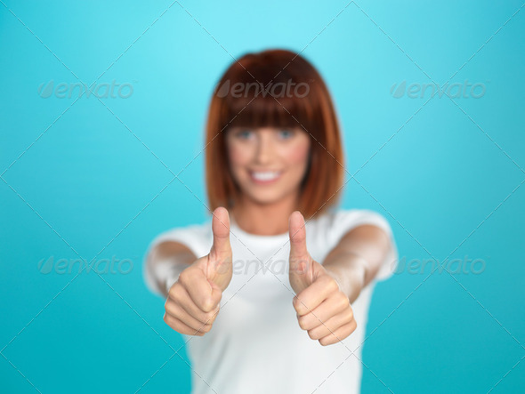 attractive woman smiling with her thumbs up - Stock Photo - Images