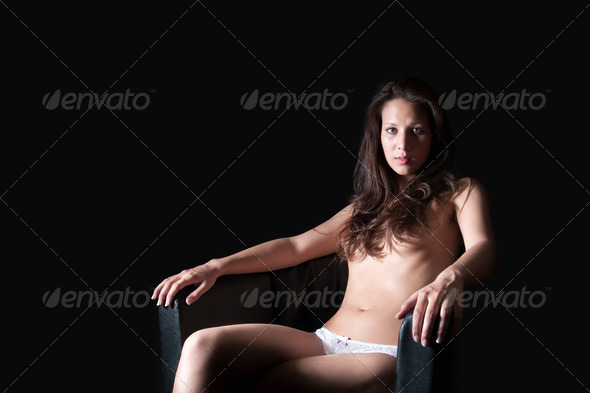 Beautiful nude woman on black armchair - Stock Photo - Images
