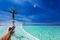 Man's legs in hammock over tropical lagoon - PhotoDune Item for Sale
