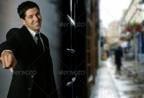 Excited young businessman smiling and pointing - Stock Photo - Images