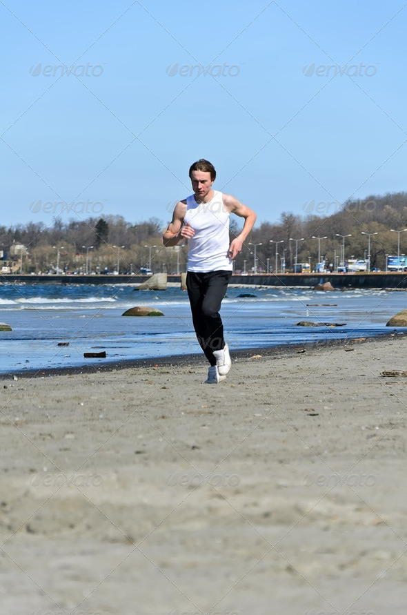 Athletic young male running on the beach - Stock Photo - Images