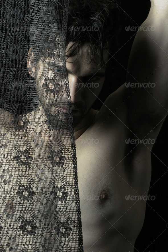 Sexy shadowy portrait of masculine male model behind dark lace - Stock Photo - Images