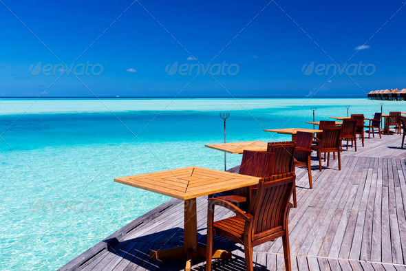 Tables and chairs at tropical beach restaurant - Stock Photo - Images