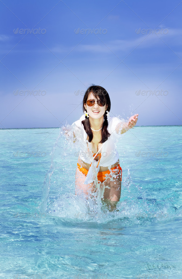 Beautiful fashion asian girl playing water in Maldive beach near the ocean - Stock Photo - Images
