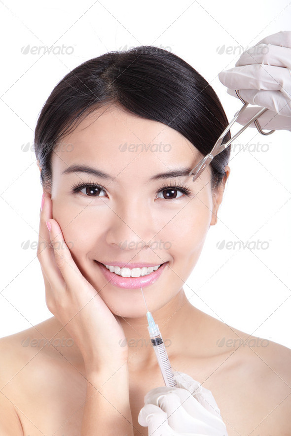 woman smile receiving a injection in her lip - Stock Photo - Images