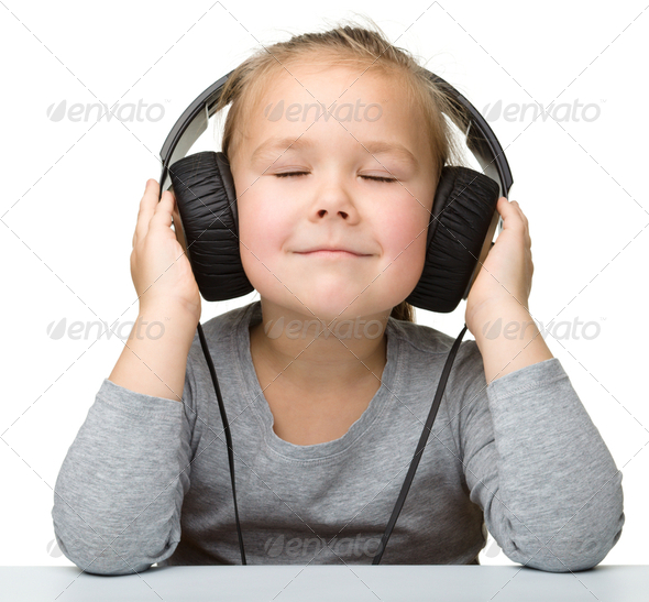 Cute little girl enjoying music using headphones - Stock Photo - Images