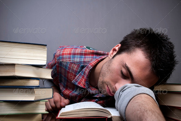 Young man sleeping on books - Stock Photo - Images