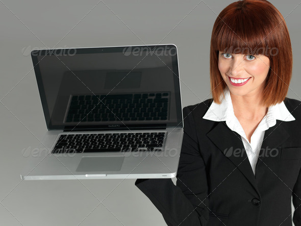 attractive, young businesswoman holding a laptop - Stock Photo - Images