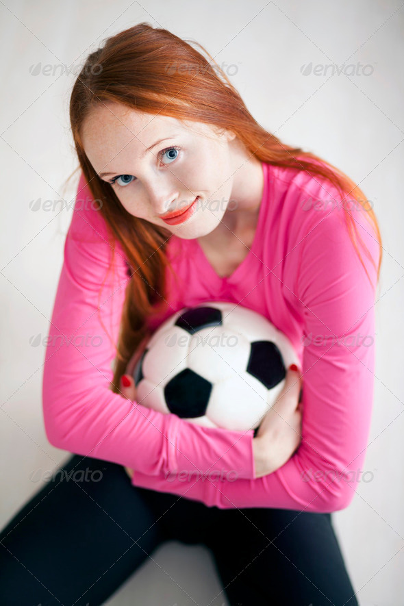 Attractive blond girl holding a soccer ball and sitting on floor - Stock Photo - Images