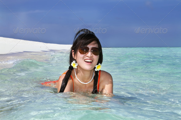 Beautiful fashion asian girl play water in sea in summer - Stock Photo - Images
