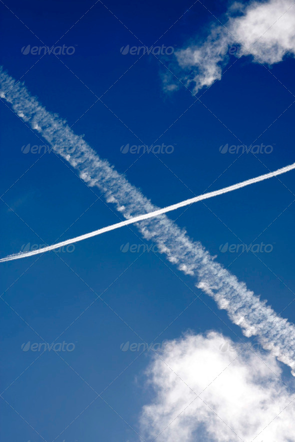 Passenger jet trails crossing in a blue sky - Stock Photo - Images