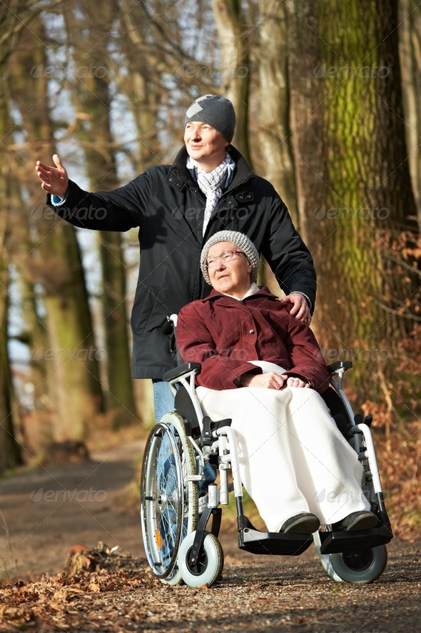 elderly woman in wheelchair walking with son - Stock Photo - Images