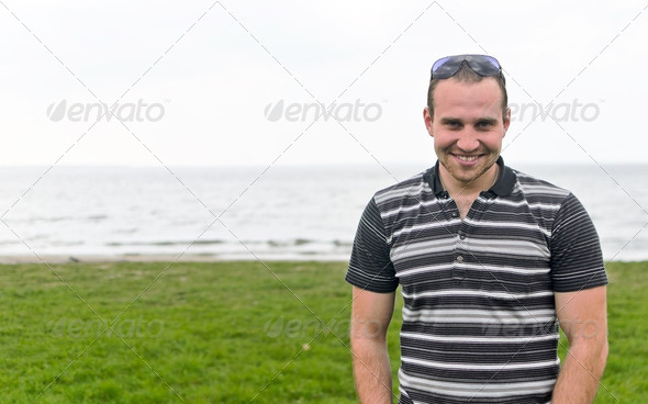 Handsome smiling man near the seaside. - Stock Photo - Images