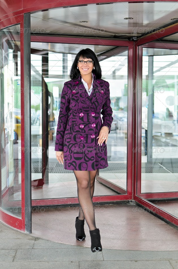 Pretty woman in a coat going thru revolving doors - Stock Photo - Images