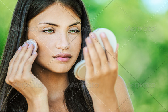 woman with bare shoulders causes powder to face - Stock Photo - Images