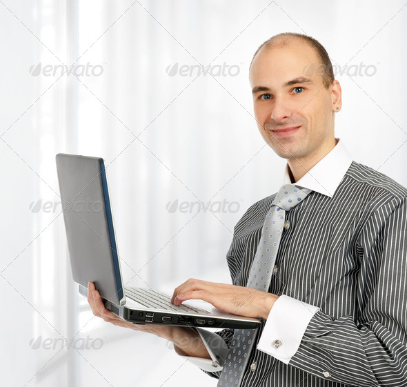 Portrait of a confident young business man with laptop - Stock Photo - Images