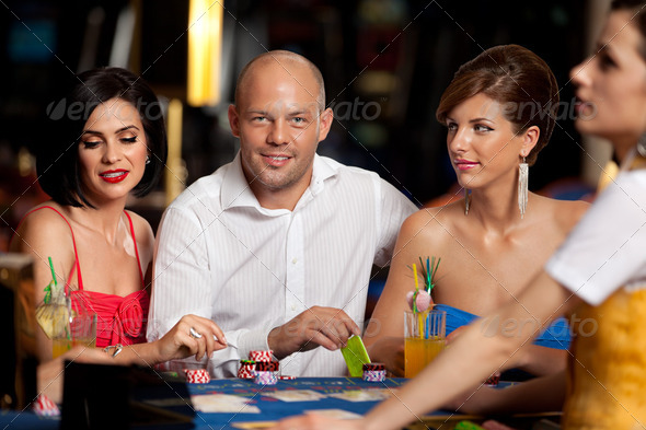 handsome blackjack player with two elegant women - Stock Photo - Images