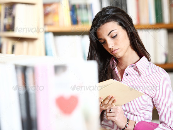 female student reading a book in library - Stock Photo - Images