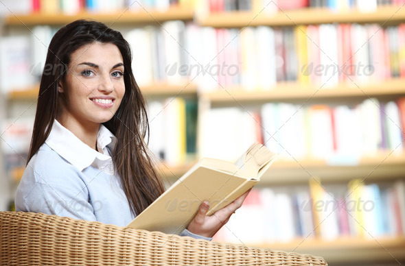 smiling female student with book in hands sitting in a chair in - Stock Photo - Images