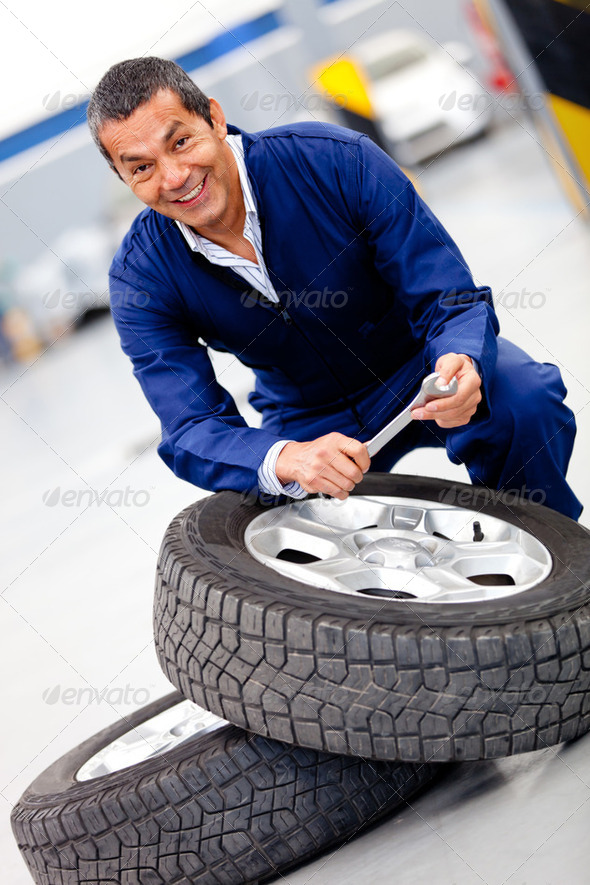 Mechanic fixing car tire - Stock Photo - Images