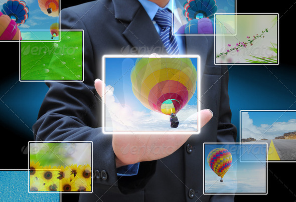 businessman hand pushing a button streaming images on a touch screen interface - Stock Photo - Images