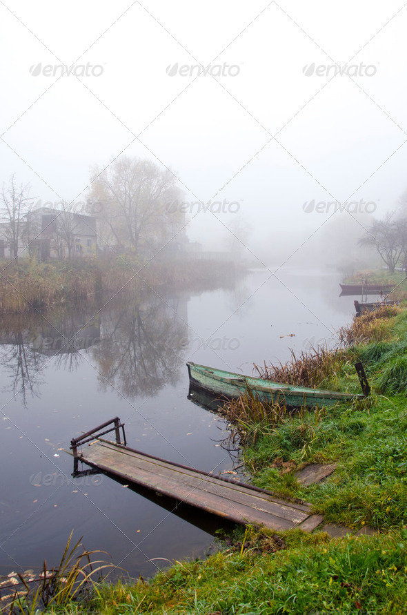Wooden boat and bridge on river sunken in fog - Stock Photo - Images