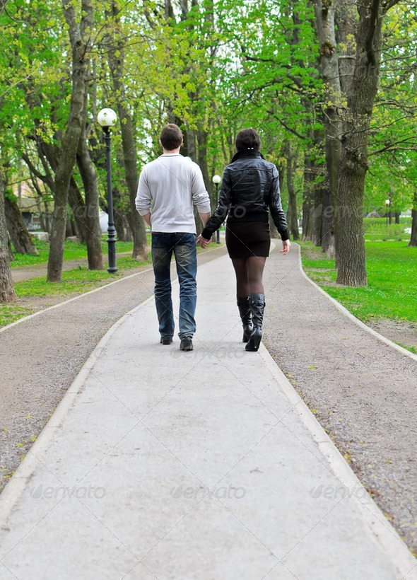 Couple walking down the road in the park. From the back - Stock Photo - Images