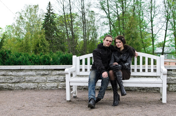 Portrait of happy couple on park bench. - Stock Photo - Images